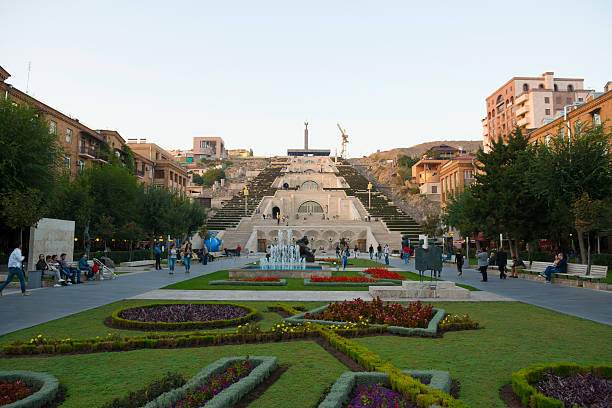Cascade stairs in Yerevan, Armenia Yerevan, Armenia - October 5, 2016: People enjoy a warm autumn evening at the base of the Cascade, a giant stairway in Yerevan, Armenia. In addition to stairs the Cascade has multiple levels with fountains and sculptures. The Cascade was designed by architects Jim Torosyan, Aslan Mkhitaryan, Sargis Gurzadyan and completed in 1980 when Armenia was part of the Soviet Union. armenian culture stock pictures, royalty-free photos & images