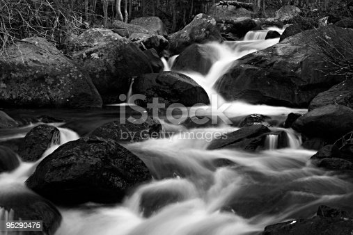 In this black-and-white time exposure the waters of Glacier Creek above Alberta Falls cascade down through a series of boulders.