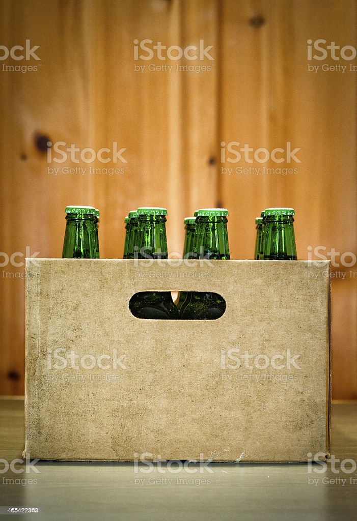 A case of beer bottles with a wood wall in the background royalty-free stock photo