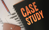 istock Case studies text written on a diary cover orange on black. Business concept. Selective focus 1245879851