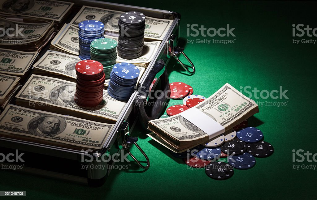 Case with dollars and chips on green cloth background stock photo