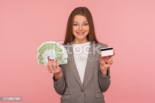 Cash deposit and loan. Portrait of happy smiling elegant businesswoman in suit jacket holding euro banknotes and credit card, satisfied with bank services. studio shot isolated on pink background