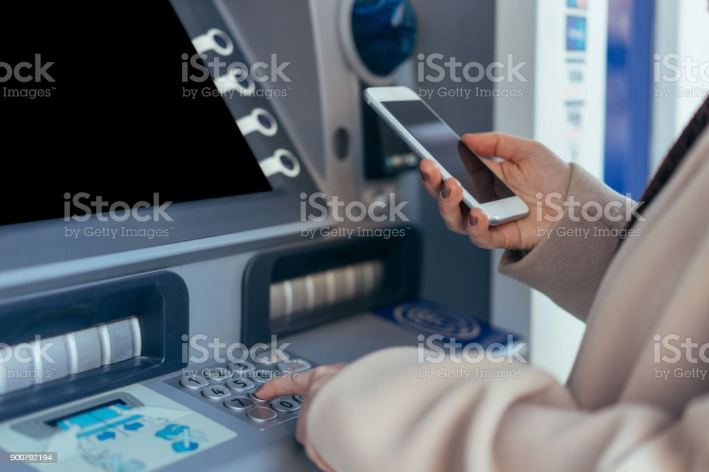 Cash dispenser with smartphone stock photo