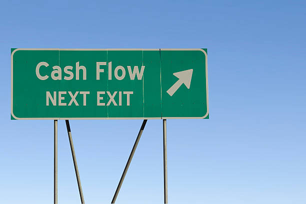 Cash Flow - Next Exit Road Green road sign with a blue sky gradient background. cash flow stock pictures, royalty-free photos & images