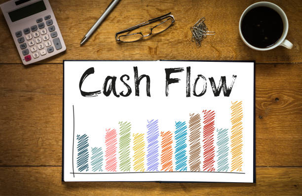 Cash flow Overhead top view of Cash Flow written in book on desk with a coloured bar chart and trend line.  Desk has coffee cup, glasses, pen and calculator cash flow stock pictures, royalty-free photos & images