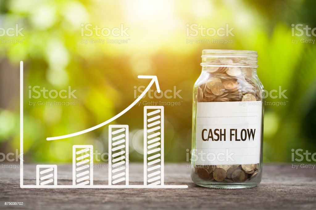 Cash Flow Word With Coin In Glass Jar and graph up. Financial Concept stock photo