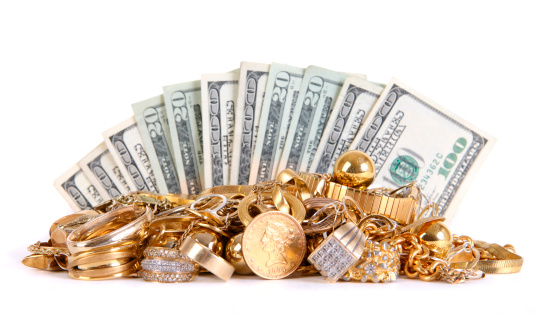 Fanned rows of money behind a stack of scrap gold.