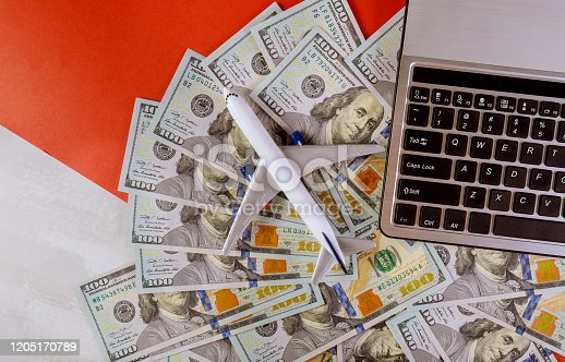 istock Cash in american dollar banknotes with plastic airplane model and computer keyboard 1205170789