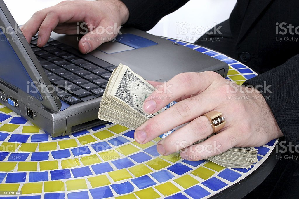 Cash In Hand Resting On Table Top Near Laptop royalty-free stock photo