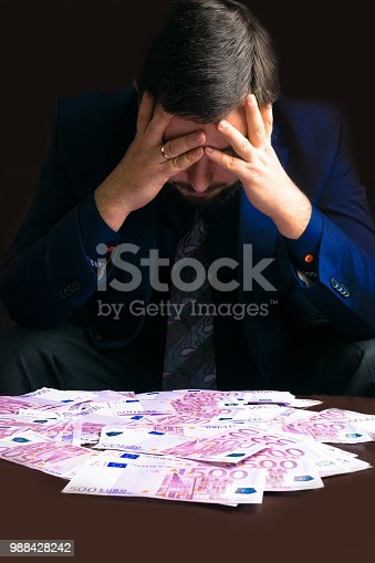 Cash Income. Businesman sitting down with his earn euro cash after a hard day, his head lowered. Man in Men's Suits. A lot of euro money. Bribe and corruption with euro banknotes.