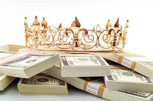 Cash is king, economic treasure and financial successful retirement conceptual idea with gold metal crown on pile of 100 dollar bills isolated on white background