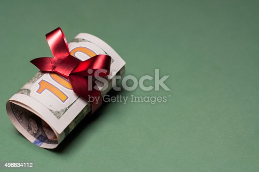 Rolled U.S. one hundred dollar bill, tied with red ribbon and a bow. The bow color suggests a Christmas gift, bonus, birthday present, or special occasion. Isolated on a green background.