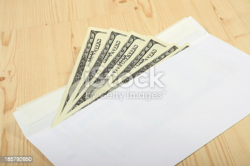 American $100 dollar notes coming out of an envelope