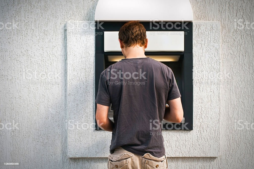 Cash withdrawal at the ATM with grey shirt royalty-free stock photo