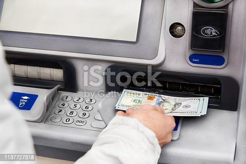istock Cash withdrawal in dollars from an ATM. 1137727318