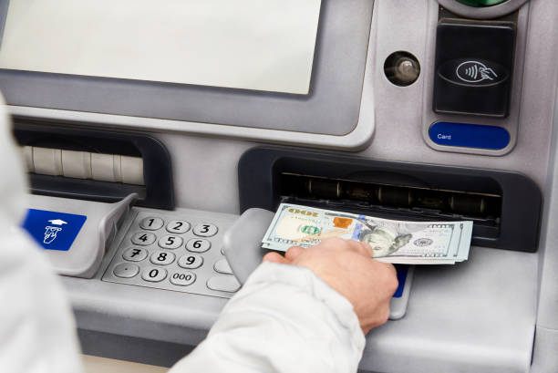 Cash withdrawal in dollars from an ATM. Cash withdrawal in dollars from an ATM. banks and atms stock pictures, royalty-free photos & images