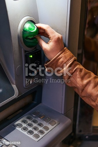 A young woman's hand withdrawing money from an ATM machine during her vacations in Venice, Italy.