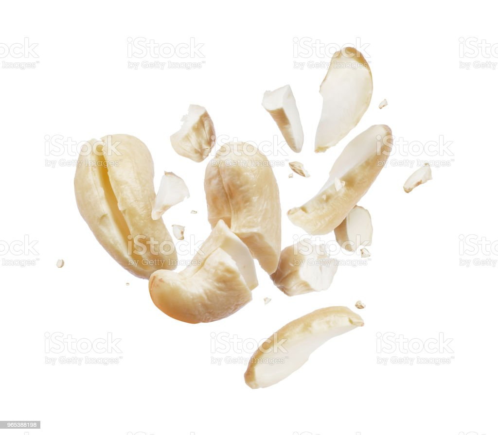 Cashew crushed into pieces close-up, isolated on white background royalty-free stock photo