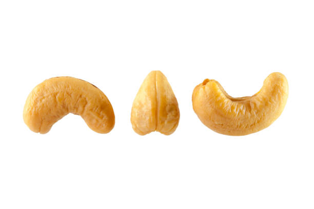 cashew nuts heap on white background - cashew stock photos and pictures