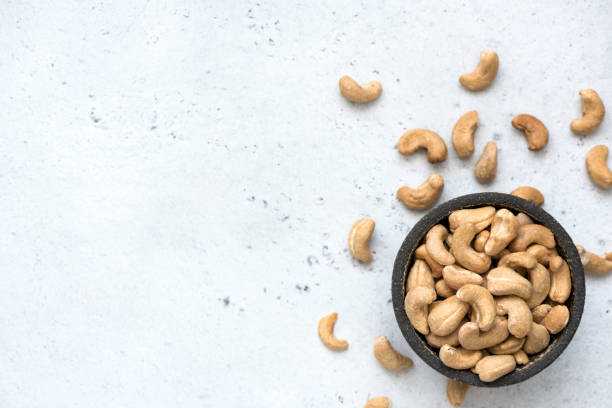 cashew nuts in bowl on grey concrete background - cashew stock photos and pictures