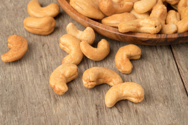 cashew nuts in wooden bowl  on woden table. - cashew stock photos and pictures