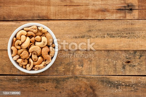 Top view of white bowl full of cashews over wooden table