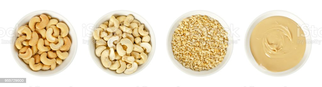 Cashews, raw and processed, in white bowls over white - foto stock