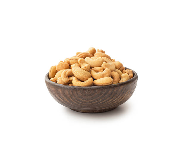 cashews with wooden bowl - cashew stock photos and pictures