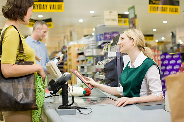 Cashier and customers at supermarket checkout stock photo