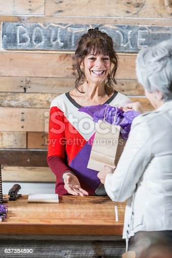 536272741istockphoto Cashier at boutique handing customer a shopping bag 637384890