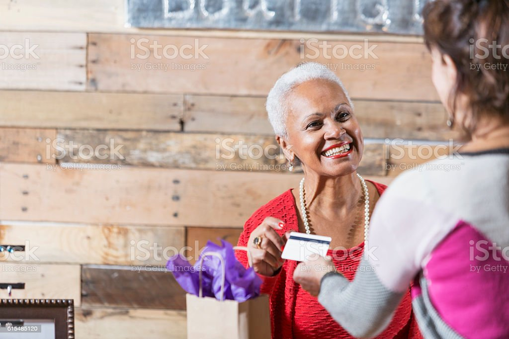 Cashier at boutique taking credit card from customer stock photo