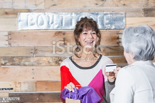 istock Cashier at boutique taking credit card from customer 615805776