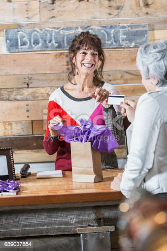 istock Cashier at boutique taking credit card from customer 639037854