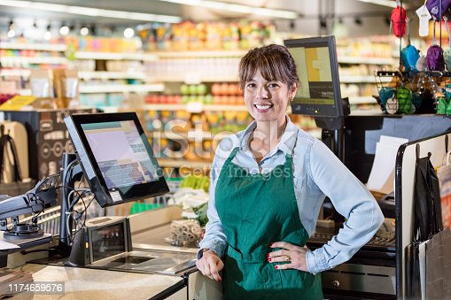 A mature mixed race Asian and Caucasian woman in her 40s working as a cashier in a supermarket. She is smiling at the camera with her hand on her hip.
