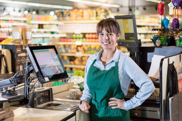 Cashier at supermarket checkout lane stock photo