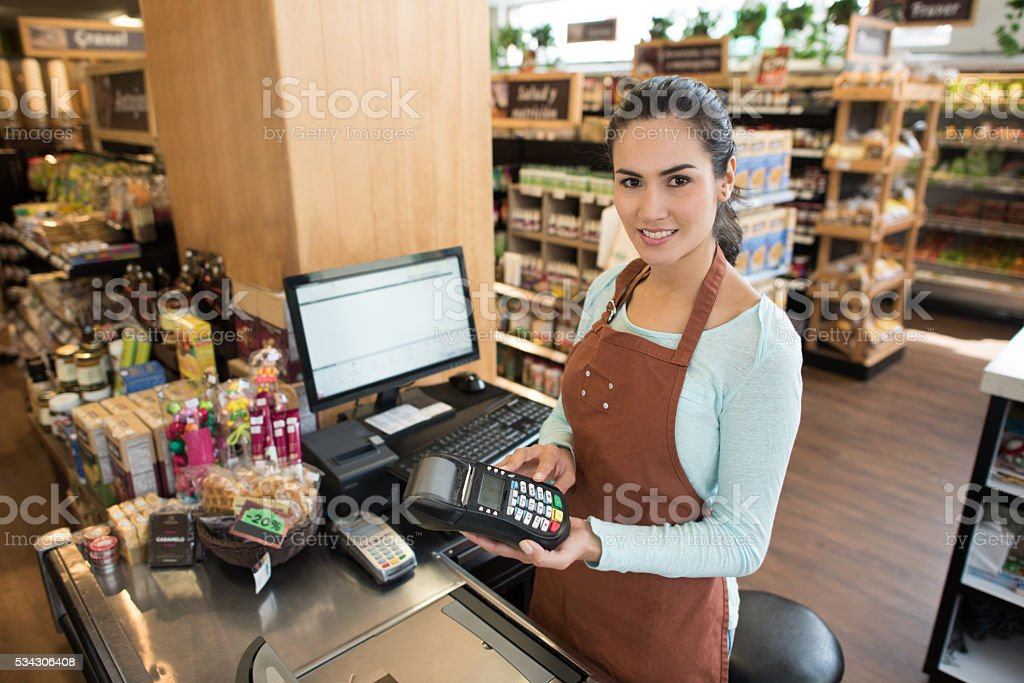 Cashier holding a credit card machine at the supermarket stock photo