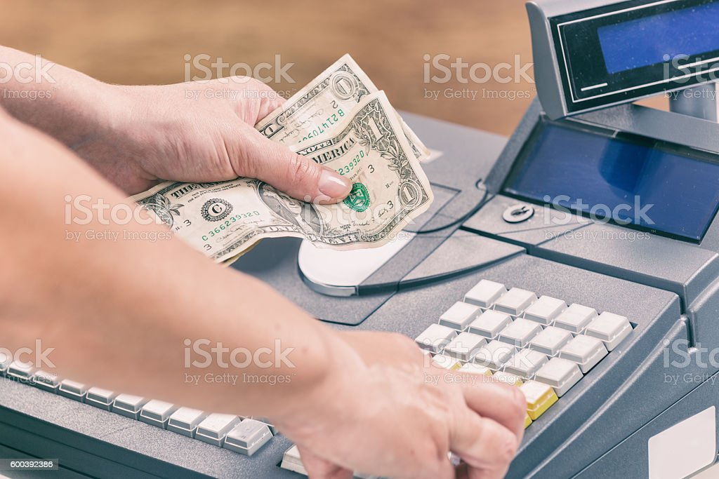 Cashier holdnig banknotes Cashier holdnig banknotes and using cash register at shop Abundance Stock Photo