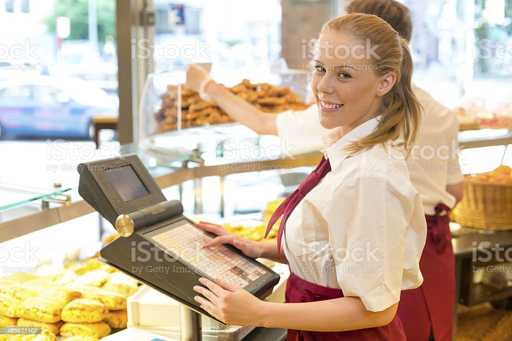 Cashier in baker's shop posing with cash register stock photo