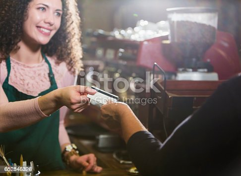 istock Cashier in coffee shop takes payment card from customer 652846326