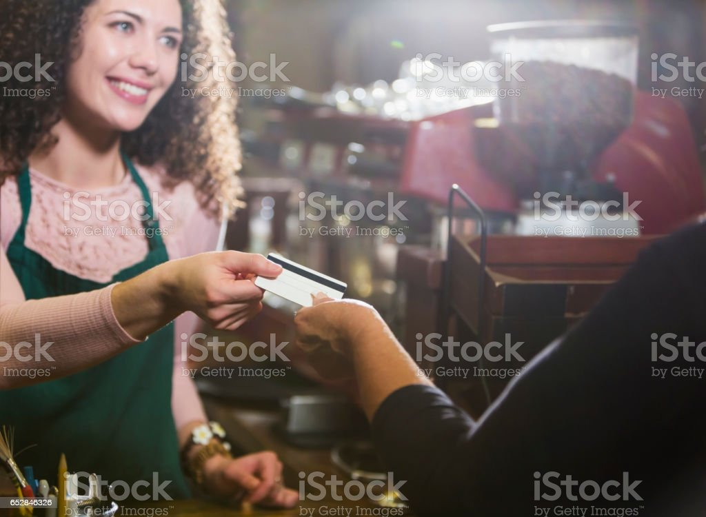 Cashier in coffee shop takes payment card from customer stock photo