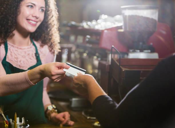 Caissier dans café prend la carte de paiement du client - Photo