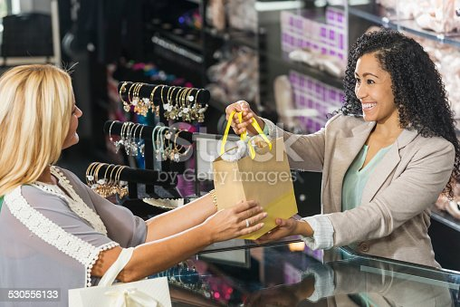 istock Cashier in retail store handing customer a shopping bag 530556133