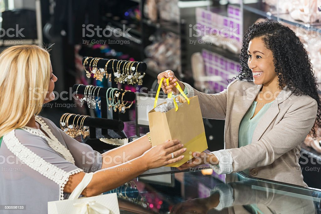 Cashier in retail store handing customer a shopping bag stock photo