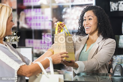 istock Cashier in retail store handing customer shopping bag 530732599