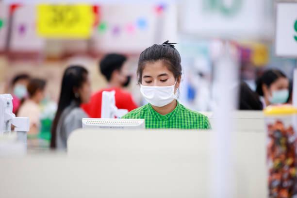 Cajero o personal de supermercado y clientes con máscara de protección médica - foto de stock