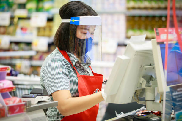 cashier or supermarket staff in medical protective mask and face shield working at supermarket - servizi essenziali foto e immagini stock