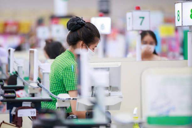 Cajero o personal de supermercado con máscara de protección médica trabajando en el supermercado - foto de stock