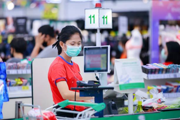 Cajero o personal de supermercado con máscara protectora médica trabajando en el supermercado. - foto de stock