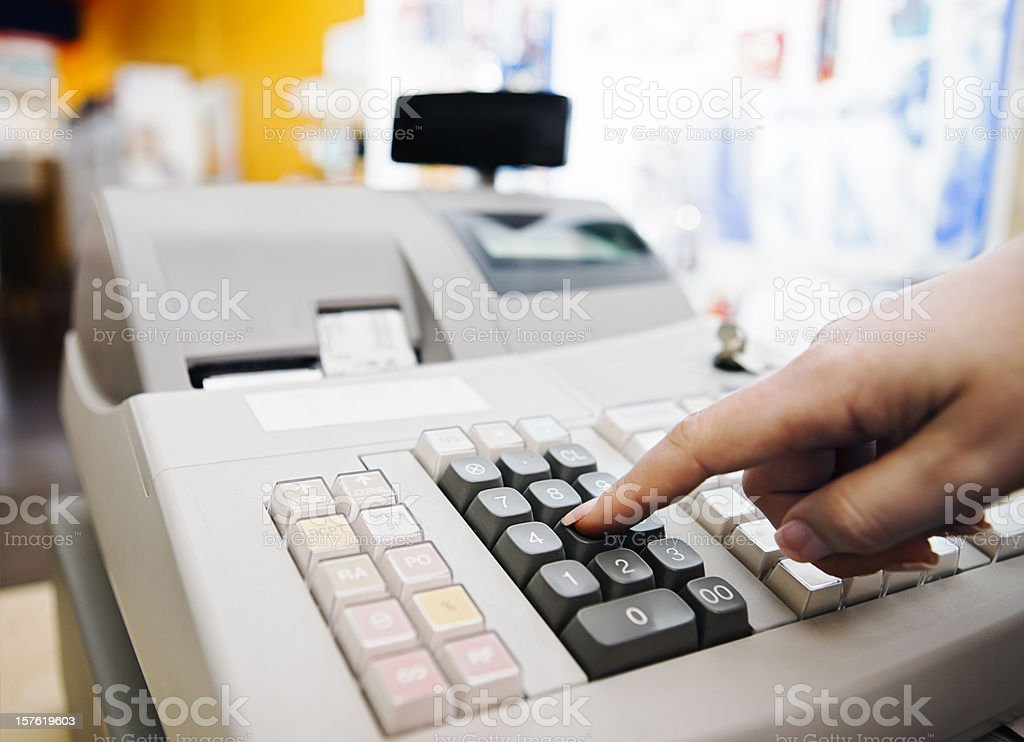 Cashier pressing buttons on electronic cash register in store royalty-free stock photo