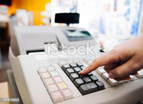 istock Cashier pressing buttons on electronic cash register in store 157619603